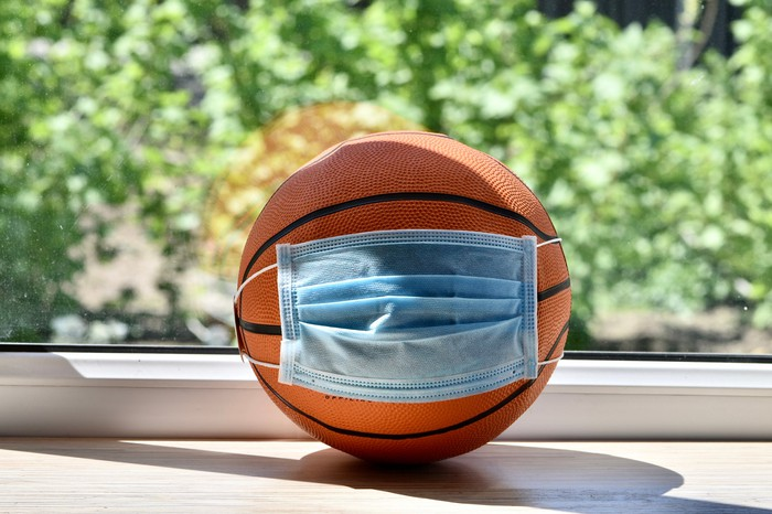 A basketball wearing a blue mask, on a tablein front of a window
