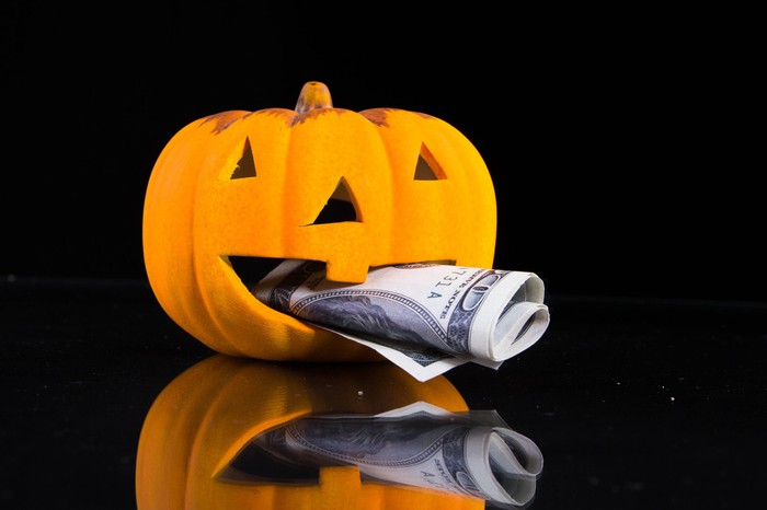 A jack o'lantern with a hundred-dollar bill in its mouth.