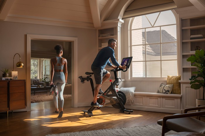 A man exercises on a Peloton stationary bike as a woman walks by inside a home with a large bay window.