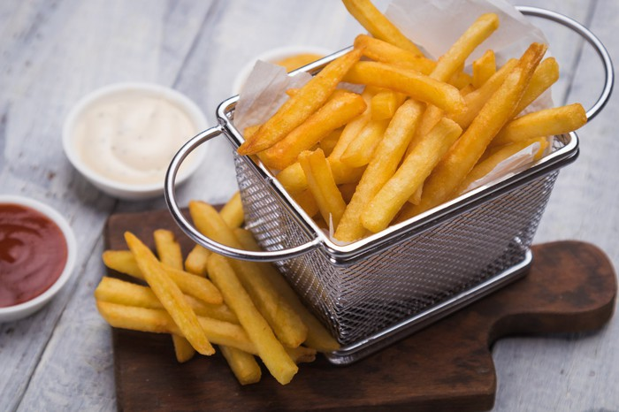 A metal basket of French fries atop a wooden cutting board.