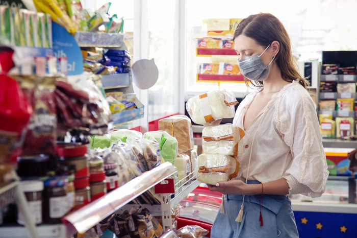 Woman shopping in a store as she wears a mask.