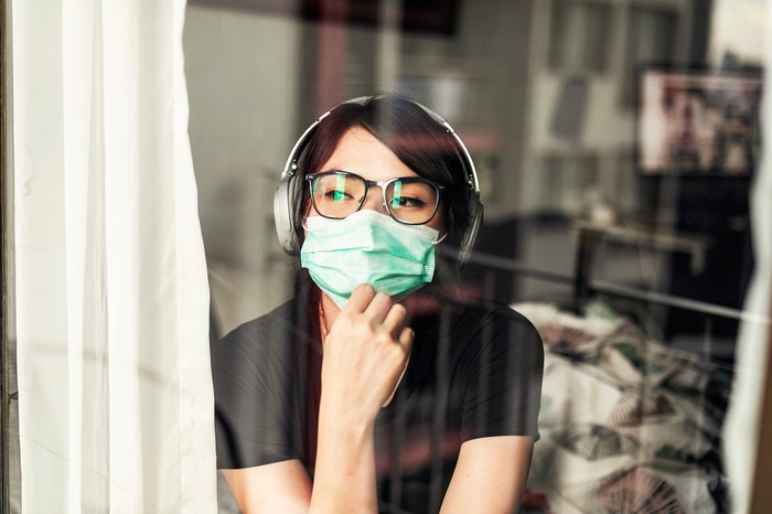 A woman wearing headphones and a surgical masks gazes out the window of a house.