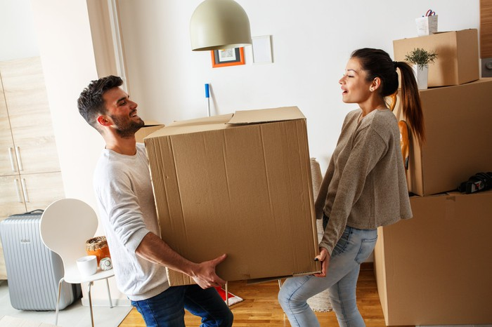 Young couple holding a moving box.
