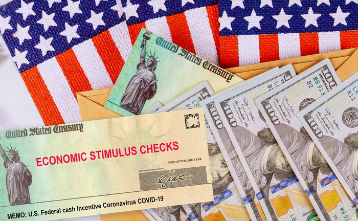 $100 bills, treasury checks and flags spread out on a table.