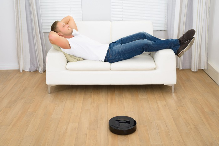A young person relaxes on a white loveseat while a vacuum robot cleans the floor.