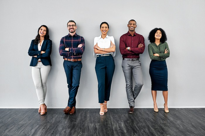 Five young professionals standing confidently against a wall