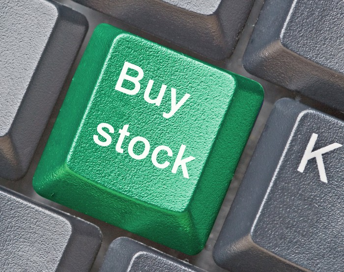"""A green """"buy stock"""" button on a gray keyboard."""