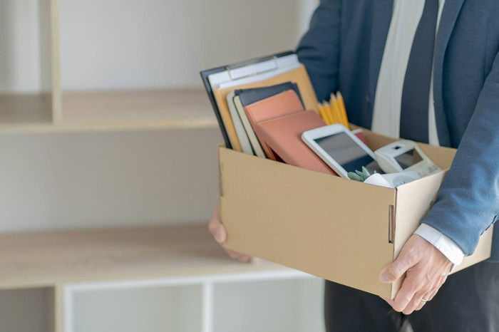 Fired person leaving office with box of supplies.
