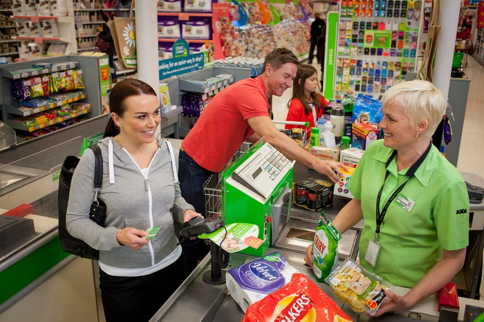 A customer checks out at an Asda grocery store.