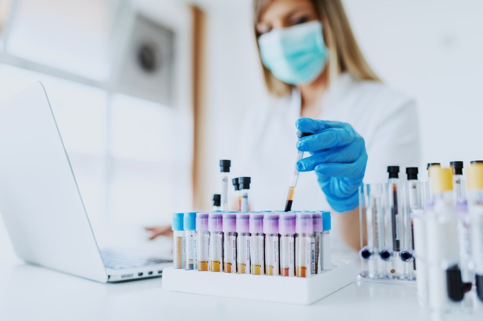 A scientist considers a test tube in a laboratory.
