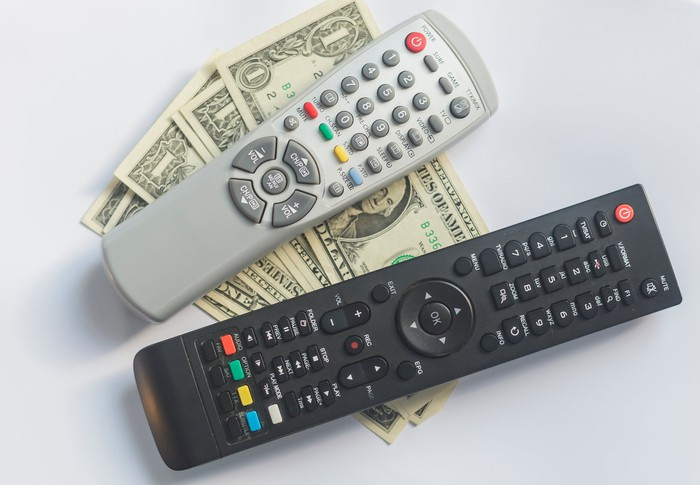 Two TV remotes resting on a stack of dollar bills.