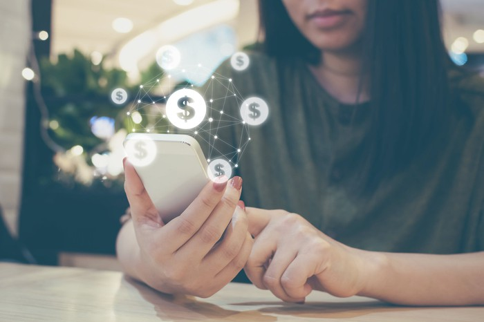 A young woman uses a smartphone surrounded by dollar-sign symbols.