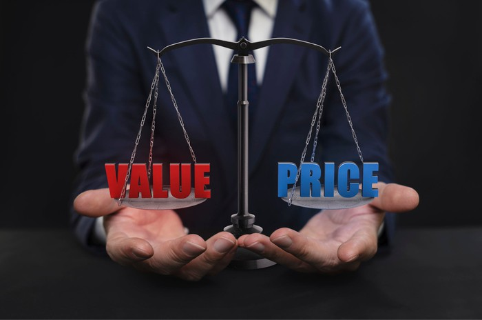 Man holding a value vs. price scale in the palms of his hands.