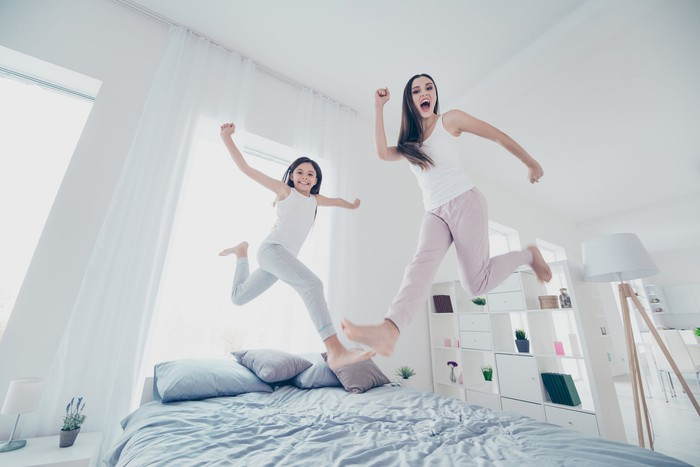 Two people jumping over a bed, with happy faces.