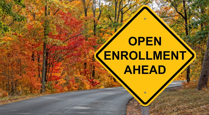 Diamond shaped sign reading open enrollment ahead on road with bright colored leaves