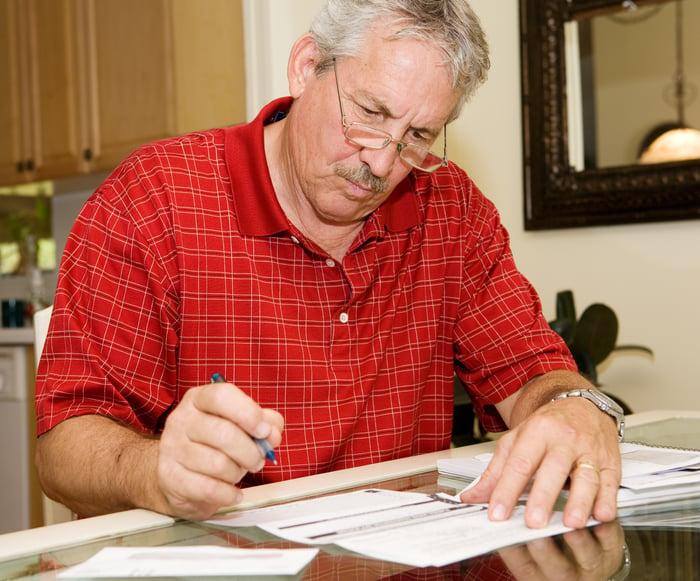 Older man holding pen over document