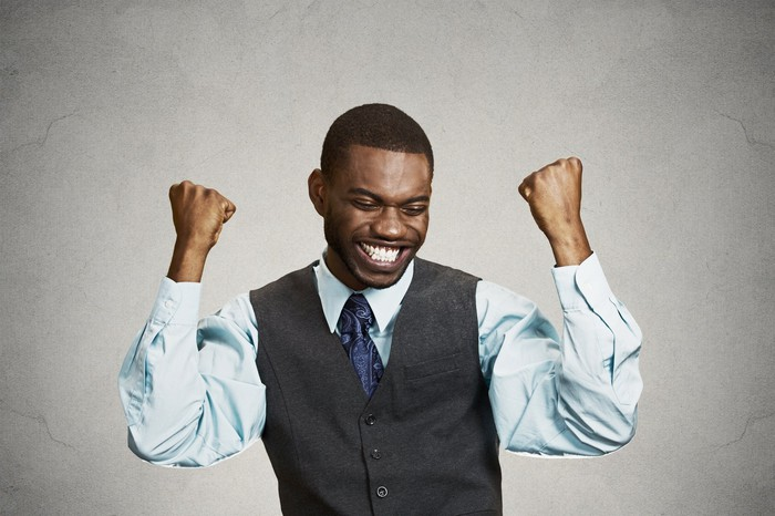 A man wearing a vest and tie has his hands raised in victory.