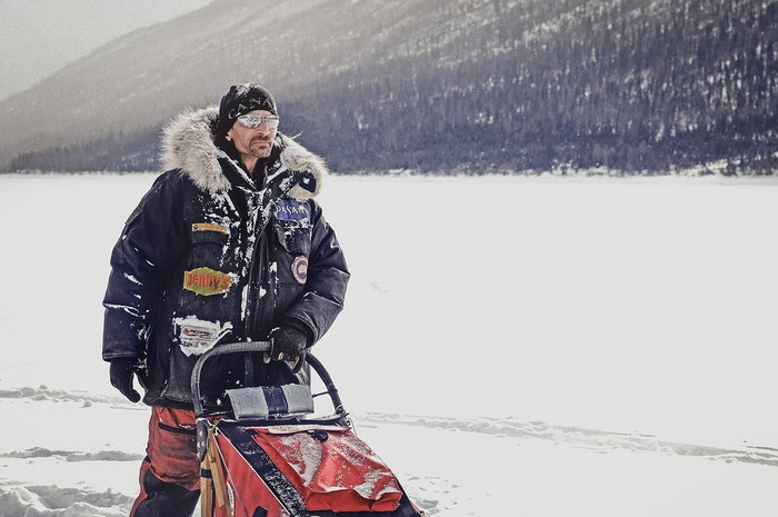 A man standing on a snowmobile in a Canada Goose jacket