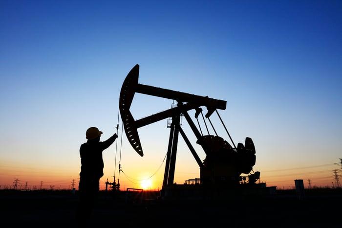Worker next to an oil pump.