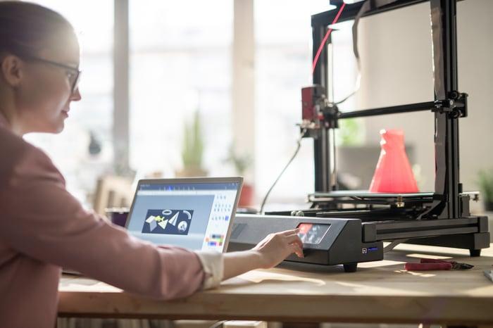 A woman uses a 3D printer.