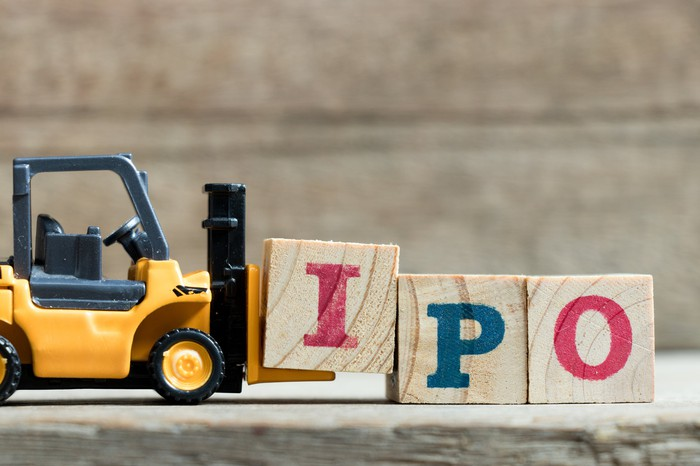 "A miniature forklift moves three wooden blocks with the letters ""IPO"" written on them."