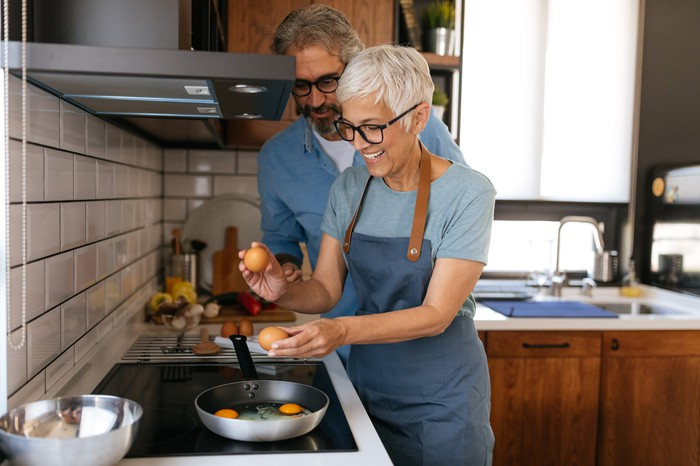 Older couple cooking eggs together.