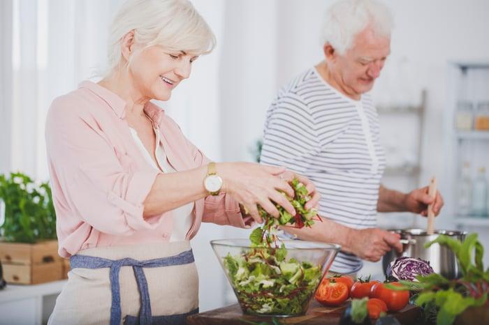 Smiling older woman making salad while older man stirs pot
