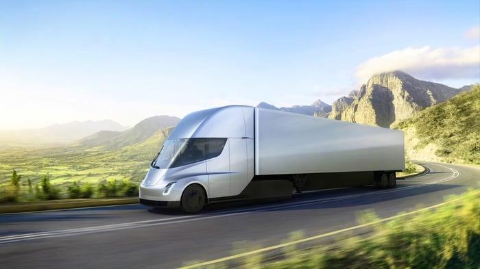 Tesla Semi truck in silver, driving on a road in a grassy mountain meadow.