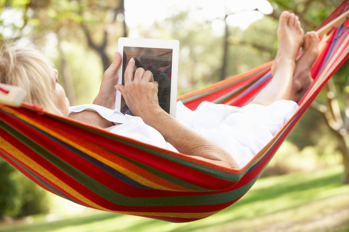 A senior woman relaxes in a hammock while reading an e-book.