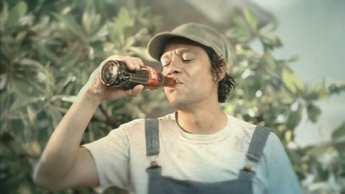 A person in overalls taking a sip from a Coca-Cola bottle.