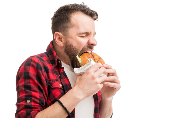 Man taking big bite out of a burger