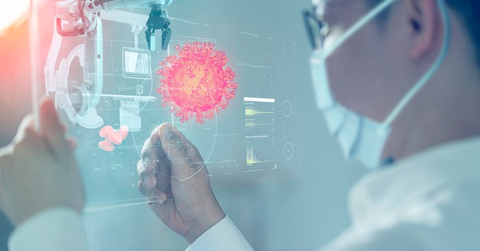 Scientist looking at a digital rendering of a coronavirus