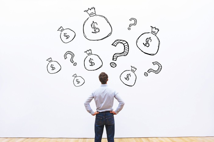 Man with hands on his hips looking at drawings on a wall of money bags and question marks