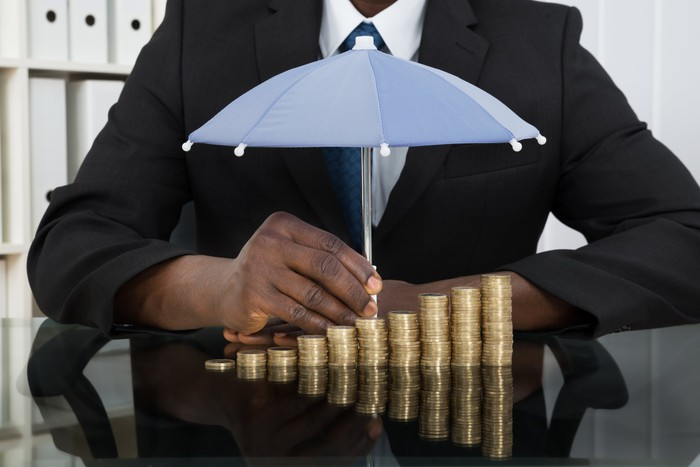 Person in a suit holding a small umbrella over stacks of gold coins.