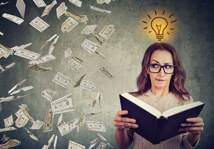 Woman holding a book with a drawing of a light bulb over her head and money flying in the air next to her