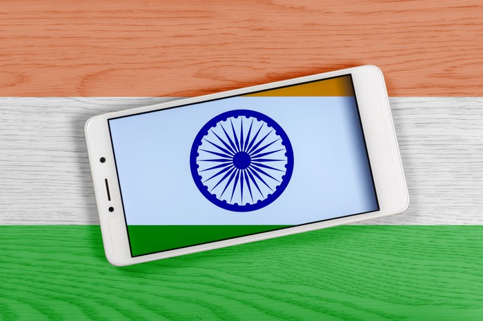 Smartphone with the Indian flag in the background.