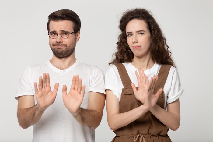 Couple giving refuse gesture.