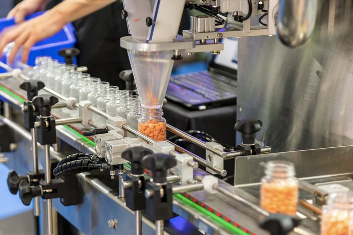 a manufacturing line of unlabeled pill bottles being filled by machine with orange pills.