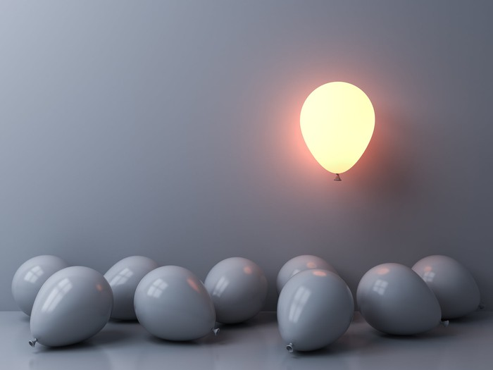 One light balloon glowing and floating above other grey balloons on grey wall background