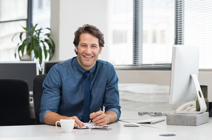 Smiling person in professional attire at desk.