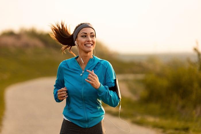 A woman jogging down a path.