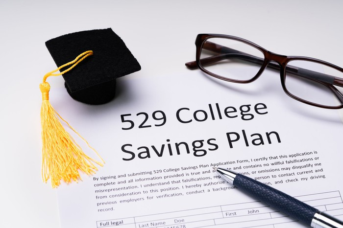 529 plan document with glasses, pen, and mortarboard