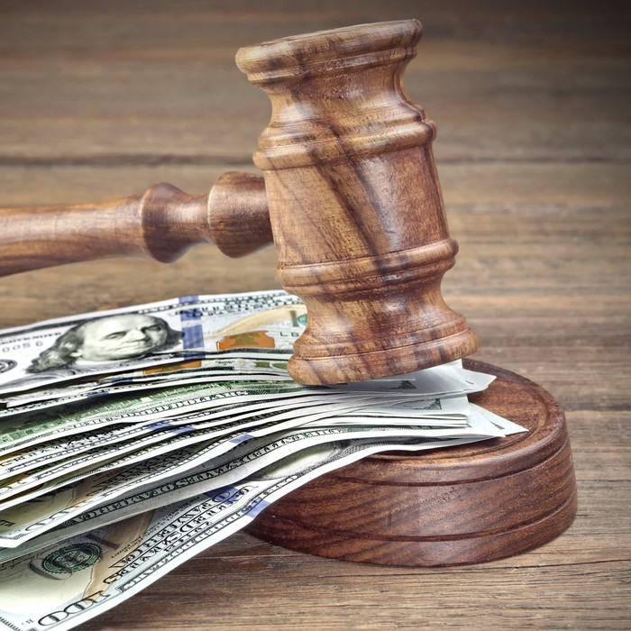 Judge's gavel on top of a money stack.