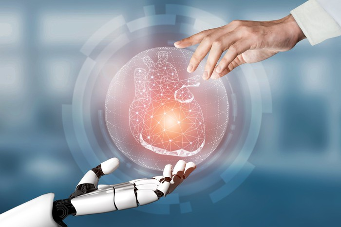 A digital imaghe of a heart hovers in the air between a doctor's hand and a robot hand.