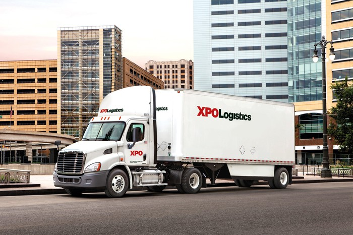 An XPO truck driving on a city street.