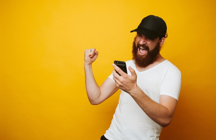 A bearded sports bro pumps his fist and smiles at his phone.