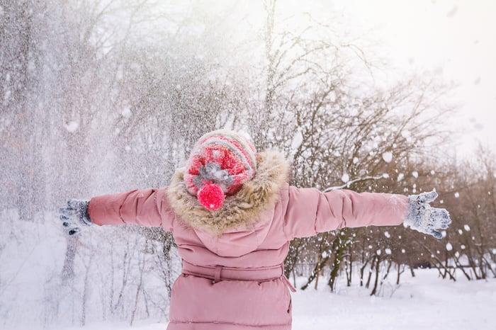 Woman enjoying a fresh snowfall.