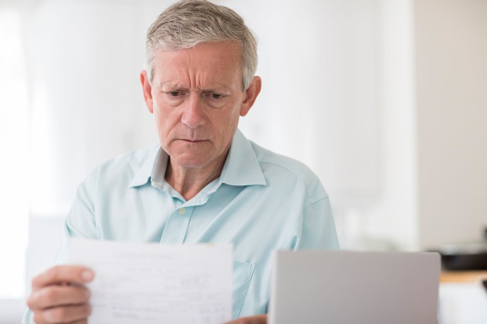 Older person with concerned expression holding document.