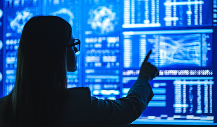 A businesswoman working with a display showing data analytics.