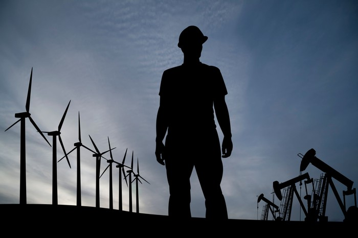A man stands between wind turbines and oil pumpjacks.